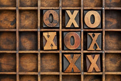 Tic-tac-toe or noughts and crosses. Game - vintage letterpress printing block X and O in wooden grunge typesetter box with dividers Stock Photos