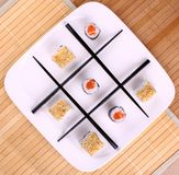 Tic tac toe play and chopsticks with sushi, close up. Tic tac toe play and chopsticks with sushi, top view Royalty Free Stock Images