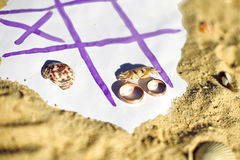 Tic Tac Toe and wedding rings on the beach. Wedding in the tropics concept Royalty Free Stock Image