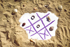 Tic Tac Toe y anillos de bodas en la playa El casarse en el concepto de las zonas tropicales Fotografía de archivo