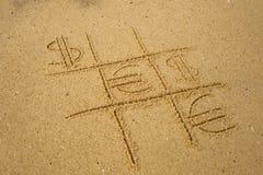 Tic-TAC-Zehenspiel mit dem Spielen von Euro- und Dollarsymbolen auf Sand Stockfotografie