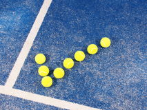 Tick symbol of Tennis balls a pristine blue artificial grass court Stock Photography