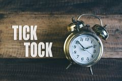 Tick tock day concept. golden alarm clock. Tick tock day concept - golden bell clock on a wooden table background with `Tick Tock` word Stock Image