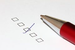 Ticked checkbox with pen. Filled survey question with pen pointing up Stock Photo