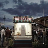 Ticket Booth. People standing around a ticket booth on the midway at dusk stock image