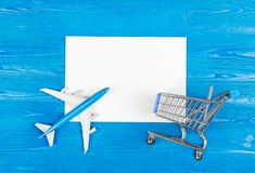 Model of airplane, grocery cart and blank sheet of paper on the blue wooden background. Travel concept. Ticket purchase. Royalty Free Stock Photos