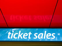 Ticket sales. Large ticket sales sign on shiny blue background reflected in red ceiling Royalty Free Stock Images