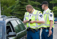 Ticket for speeding. HAAKSBERGEN, NETHERLANDS - JUNE 09: A policeman is writing a ticket for a car driver who was speeding, june 09, 2011 in the Netherlands Royalty Free Stock Photos