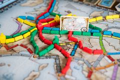 Ticket to ride board game. A lot of trains and card with road from berlin to rome on map. royalty free stock photos