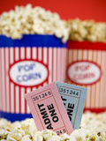 Tickets and fun. Two popcorn buckets over a red background. Movie stubs sitting over the popcorn Royalty Free Stock Image