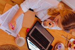 Student wearing white shirt ticking the answers for test. Ticking the answers. Top view of blonde-haired student wearing white shirt ticking the answers for test royalty free stock image