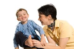 Tickle. Mom tickling son's feet on white isolated background Stock Image