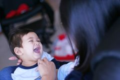 Tickle time with mom. Mother tickling her baby boy, causing him to laugh. Baby is part asian, part scandinavian Stock Photography