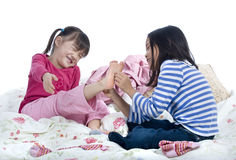 Tickle toes. Two sisters playing on the bed tickling toes Stock Photography