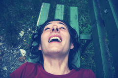 Tickled woman laughing on a bench Stock Photo