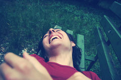 Tickled woman laughing on a bench Stock Image