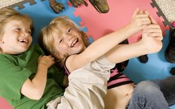 Tickling!. Adorable twins tickling each other on the playroom floor Royalty Free Stock Photography
