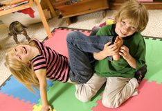 Tickling!. Adorable twins tickling each other on the playroom floor Stock Photo