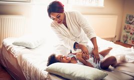 Tickling attack. African American mother and daughter playing on bed. Space for copy royalty free stock images