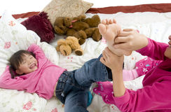 Tickling feet. Two sisters playing on the bed, tickling feet Royalty Free Stock Photography