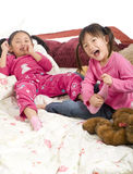 Tickling feet. Two sisters playing on the bed, tickling feet Stock Photos