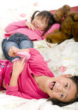 Tickling feet. Two sisters playing on the bed, tickling feet Stock Images