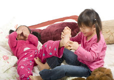 Tickling feet. Two sisters playing on the bed, tickling feet Stock Photography