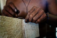 Ticuna indian tribal member stitching a tree bark artifact together royalty free stock photos