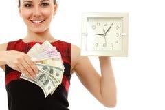 Tid är pengar - den gladlynt innehavklockan för affärskvinnan och kontant in Arkivfoton