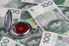 Tid är pengar, polerar 100 zlotysedlar med den traditionella klockan Royaltyfri Fotografi