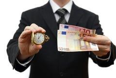 Tid är pengarbegreppet med affärsmannen med pengar- och fackwat Arkivfoton