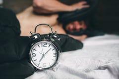 tid att up vaket Trött man i den inte lyckliga sängen Mogna den hållande ringklockan för grabben, medan kontrollera tid för arbet arkivbilder