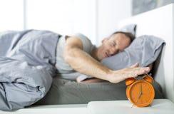 tid att up vaket Trött man i sängen fotografering för bildbyråer