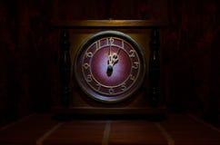 Tid begrepp - den wood klockaframsidan för tappning med grungetextur på mörker - röd rödbrun gardinbakgrund, en nolla-klocka Arkivfoton