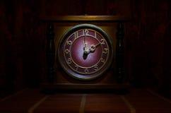 Tid begrepp - den wood klockaframsidan för tappning med grungetextur på mörker - röd rödbrun gardinbakgrund, för klockalunch för  Arkivbild