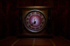 Tid begrepp - den wood klockaframsidan för tappning med grungetextur på mörker - röd rödbrun gardinbakgrund, klocka för nolla ått Royaltyfri Fotografi