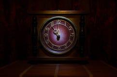 Tid begrepp - den wood klockaframsidan för tappning med grungetextur på mörker - röd rödbrun gardinbakgrund, klocka för nolla elv Royaltyfri Fotografi