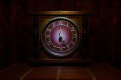 Tid begrepp - den wood klockaframsidan för tappning med grungetextur på mörker - röd rödbrun gardinbakgrund, klocka för nolla fem Fotografering för Bildbyråer