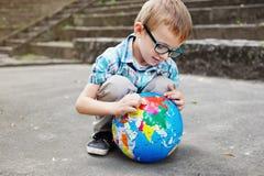 Tid för skola. Unge med jordklotet. Royaltyfri Fotografi