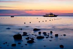 tid för solnedgång för fartygliggandehav Royaltyfri Bild