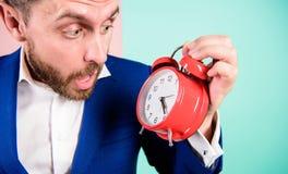 Tid ledningexpertis Hur mycket tid lämnade brukar stopptid tid att fungera För affärsmanhåll för man skäggig förvånad klocka royaltyfri bild