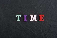 Tid ord på svart brädebakgrund som komponeras från träbokstäver för färgrikt abc-alfabetkvarter, kopieringsutrymme för annonstext Arkivbilder