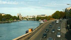 Tid schackningsperiod av biltrafik på den Seine River invallningen i Paris och den avlägsna Notre-Dame domkyrkan, Frankrike Arkivbild