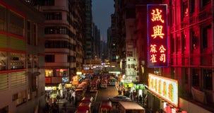 Tid schackningsperiod av den upptagna gatan med trafik och gångare av Mong Kok på natten i Hong Kong arkivfilmer