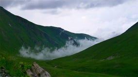 Tid schackningsperiod av dimma och moln som rullar över den gröna dalen för berg i den Kavkaz regionen lager videofilmer
