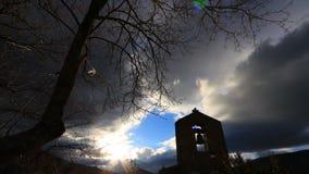 Tid schackningsperiod av ett kristet kors p? en fransk kyrktorn med apokalyptiska moln