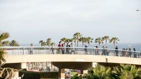 Tid schackningsperiod av folk som går över en bro Royaltyfri Bild
