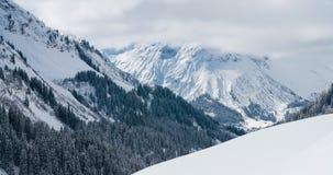 Tid schackningsperiod av moln över en alpin dal med snö täckt bergblast lager videofilmer