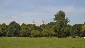 Tid schackningsperiod av Munich horisont från Englischer Garten, Tyskland Lokaler och turister tycker om en varm sommardag i park arkivfilmer