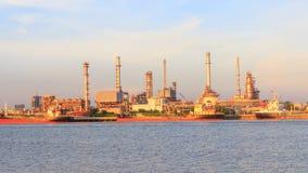 Tid schackningsperiod av oljeraffinaderiet på floden i solnedgångtid arkivfilmer